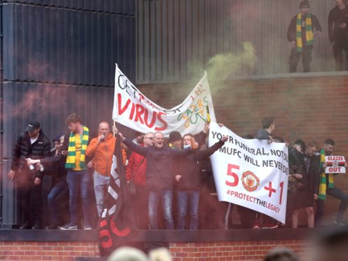 Fans holds up banners as they protest against the Glazer family at Old Trafford (Barrington Coombs/PA)