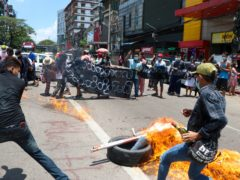 """Anti-coup protesters burn tires and chant slogans with banner read """"The Kamayut strike will be fight for to the end when we get victory"""" during the demonstration against the military coup in Kamayut township Yangon, Monday, May 3, 2021. (AP Photo)"""