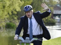 Prime Minister Boris Johnson waves as he rides a bike along the towpath of the Stourbridge canal in the West Midlands, whilst on the local election campaign trail (Rui Vieira/PA)