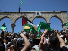 Worshippers wave Hamas and Palestinian flags (Mahmoud Illean/AP)