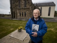 Patsy Mullan, brother of Father Hugh Mullan, visits his grave at St Patrick's Church in Portaferry (Liam McBurney/PA)