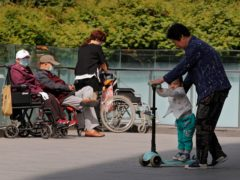 A woman plays with a child near elderly people in wheelchairs in Beijing (Andy Wong/AP)