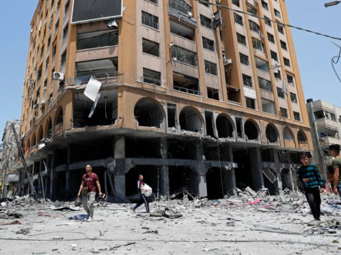 People inspect the rubble of a damaged building which was hit by an Israeli air strike in Gaza City (Adel Hana/AP)