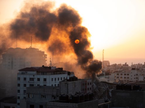 Smoke is seen from a collapsed building after it was hit by Israeli air strikes on Gaza City (Khalil Hamra/AP)