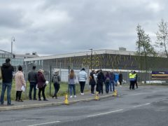 People queue for the vaccination centre at the Essa Academy in Bolton (PA)