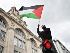 A demonstrator waves a Palestinian flag whilst sat atop a traffic light in London (PA)