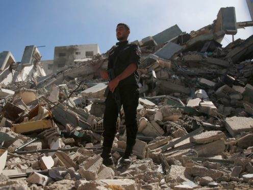 A policeman stands in the rubble of the building that housed The Associated Press offices in Gaza City (Hatem Moussa/AP)