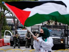 A demonstrator waves the flag of Palestine during a protest in Los Angeles (Ringo HW Chiu/AP)