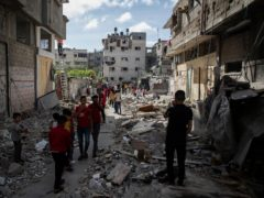 Palestinians walk amid the rubble of a house that was hit by early morning Israeli airstrikes, in Gaza City, Monday, May 17, 2021. (AP Photo/Khalil Hamra)