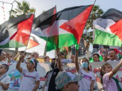 Children wave Palestinian flags during a protest supporting the children in Gaza, in the West Bank city of Ramallah (Nasser Nasser/AP)