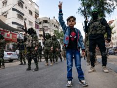 Children stand with Hamas militants as they parade through the streets (John Minchillo/AP)