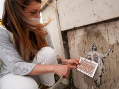 Artist Alessia Babrow holds the Vatican stamps next to her street art during an interview with the Associated Press at the Vatican (Andrew Medichini/AP)