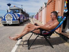 Stuart Henderson enjoys the sunshine from his beach hut on Bournemouth beach (Andrew Matthews/PA)