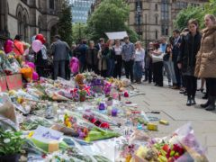 People look at flowers outside the Town Hall in Albert Square, Manchester (Peter Byrne/PA)