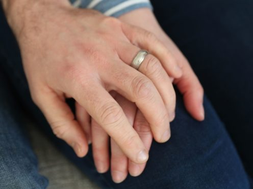 A married couple hold hands (Andrew Matthews/PA)