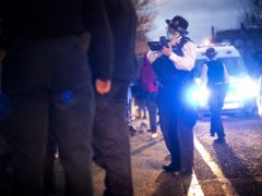 A police officer uses her radio during a stop and search (Victoria Jones/PA)