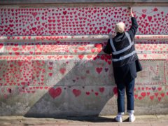 A volunteer adds hearts to the National Covid Memorial Wall (Dominic Lipinski/PA)