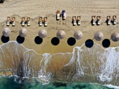 A woman enjoys the sun at Plaka beach on the Aegean island of Naxos (Thanassis Stavrakis/AP)