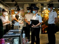 Officers from the Food and Environmental Hygiene Department ask questions to a staff, left, at the June 4 Memorial Museum in Hong Kong (Vincent Yu/AP)