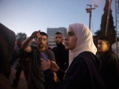 Palestinian activist Muna al-Kurd, center, stands with other activists as Israeli police approach their friends repairing a mural that was defaced by a Jewish settler, in the Sheikh Jarrah neighbourhood of east Jerusalem (Maya Alleruzzo/AP)