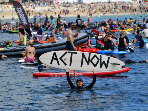 Protesters take part in a paddle out, organised by Surfers Against Sewage, on Gyllyngvase Beach near Falmouth (Ben Birchall/PA)