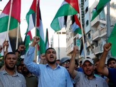 Protestors wave Palestinian flags while chanting anti-Israeli slogans during a protest against a march by Jewish ultranationalists through east Jerusalem, along the streets of Gaza City, Tuesday, June 15, 2021. (AP Photo/Adel Hana)