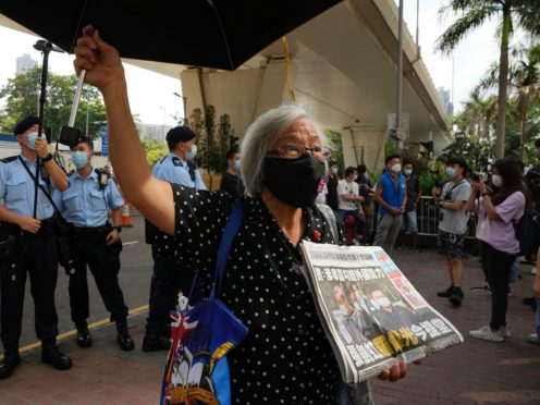 A pro-democracy activist holding a copy of Apple Daily newspaper protests outside the court in Hong Kong (Kin Cheung/AP)