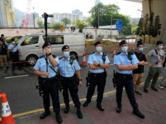 Police officers stand guard outside a court in Hong Kong (Kin Cheung/AP)
