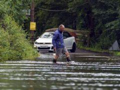 A man wades through a flooded road near Swallowfield (Steve Parsons/PA)