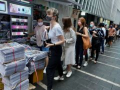 People queue up for last issue of Apple Daily at a newspaper booth at a downtown street in Hong Kong (Vincent Yu/AP)