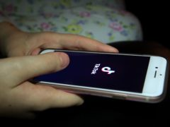 A young girl uses the TikTok app on a smartphone (Peter Byrne/PA)