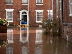 Residents on a flooded street in Bewdley, Worcestershire, after the River Severn burst its banks (PA)