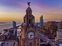 The sun sets behind the Royal Liver Building in Liverpool (PA)