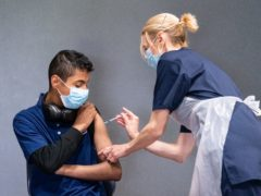 Nurse Sonia Wilson (right) vaccinates eighteen-year-old Cameron Ladd (left) with the Pfizer Covid-19 vaccine at a vaccination centre at Adwick Leisure Centre in Doncaster (Danny Lawson/PA)