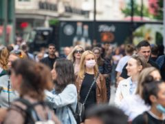 A woman wearing a face mask among a crowd of pedestrians on Oxford Street, (PA)