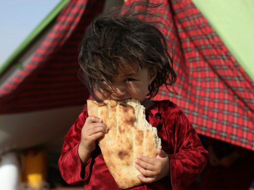An internally displaced Afghan girl whose family fled their home due to fighting between the Taliban and Afghan security personnel, eats bread (Rahmat Gul/AP)