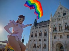 An unidentified drag queen waves a rainbow flag during an LGBT rights demonstration in front of the Hungarian Parliament building in Budapest (Bela Szandelszky/AP)