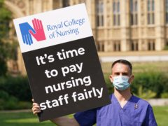 A Nurse with a placard outside the Royal College of Nursing (RCN) in Victoria Tower Gardens, London (Jonathan Brady/PA)