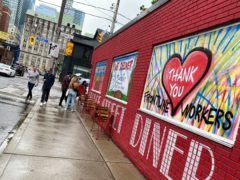 People line up to dine at a restaurant that has painted its walls to support the frontline workers in Toronto, Canada (Kamran Jebreili/AP)
