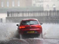 A car drives through flood water in Horse Guards Road in central London (Victoria Jones/PA)