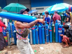 FILE – In this July 28, 2021, file photo, A man carries an oxygen tank while walking past people waiting with oxygen tanks in need of refill outside the Naing oxygen factory at the South Dagon industrial zone in Yangon, Myanmar. Supplies of medical oxygen are running low, and the government has put restrictions on its private sale in many places, saying it is trying to prevent hoarding. (AP Photo, File)