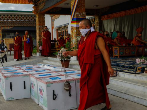 This photograph provided by UNICEF shows monks from Paro's monastic body perform a ritual as 500,000 doses of Moderna COVID-19 vaccine gifted from the United States arrived at Paro International Airport in Bhutan (UNICEF via AP)