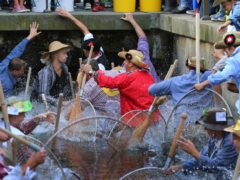 Fischertag participants compete to catch the biggest fish in a Bavarian stream (Karl-Josef Hildenbrand/dpa via AP)