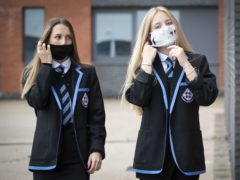 Leah McCallum and Rebecca Ross, S4 students at St Columba's High School, Gourock, put on their protective face masks as the requirement for secondary school pupils to wear face coverings when moving around school comes into effect from today across Scotland (PA)