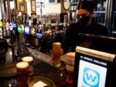 Bar staff pour drinks (Jacob King/PA)
