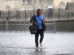 A man walks through flood water in in central London. Thunderstorms are being forecast (PA)