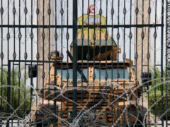 Barbed wire and a military armoured personnel carrier block a side entrance of the Tunisian parliament (Hassene Dridi/AP)