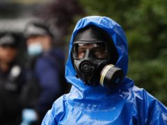 Police officers in bio-hazard suits and breathing apparatus search a property in Brixton (Aaron Chown/PA)