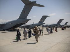 Handout photo blurred by the Ministry of Defence showing members of the UK Armed Forces leading evacuees at Kabul airport (LPhot Ben Shread/MoD/PA Wire)