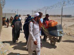 Afghan families enter Pakistan through a border crossing (Jafar Khan/AP)